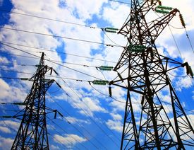image of electricity pylon  - Two electricity pylons against cloudy sky - JPG