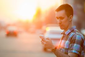 pic of scroll  - Young man holding mobile phone using smartphone app scrolling looking at screen standing on sunny street with transport vehicles on the background - JPG