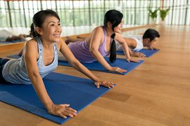 stock photo of senior class  - Senior people doing cobra pose at the yoga class - JPG