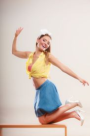 stock photo of up-skirt  - Alluring seductive pretty pin up girl wearing hairband bow skirt and high heels - JPG
