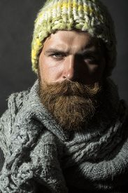 picture of long beard  - Portrait of gloomy unshaven homeless man with long beard and handlebar moustache in knitted yellow hat and grey scarf looking forward standing on black background vertical picture - JPG