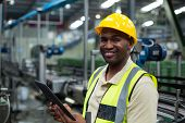 Portrait of smiling factory worker using a digital tablet in the factory poster