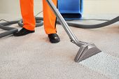 Cleaning service concept. Dry cleaners employee removing dirt from carpet in flat, closeup poster