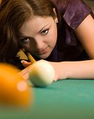 Beautiful young woman playing billiards