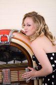 stock photo of jukebox  - Cute blond girl standing next to her jukebox kissing it - JPG