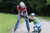 Preschooler falls over while rollerblading with mother in the park