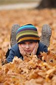 6 years old child lying prone in autumn leaves in a park. Kid has fun playing in fall leaves.
