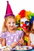 Birthday child clown eating cake with girl together. Kid with messy face have tier cake fight on iso poster