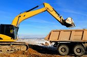 pic of boom-truck  - Excavator loading dump truck tipper at open cast over blue sky in winter - JPG