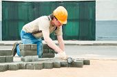 foto of bricklayer  - mason worker making sidewalk pavement with stone blocks - JPG