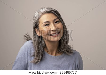 poster of Attractive Senior Asian Woman Broadly Smiles At Camera. Beautiful Grey-haired Woman Lifts Her Right