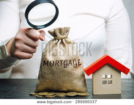 poster of A Female Hand Is Holding A Magnifying Glass Over A Money Bag With The Word Mortgage And A Wooden Hou