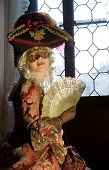 image of marquise  - Woman in renaissance mask with fan dressed in period costume with lace and jewelry and tricorn hat looking tempting in front of big window - JPG