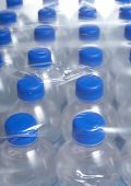 stock photo of bottle water  - Rows of bottled water bottles in plastic wrap - JPG