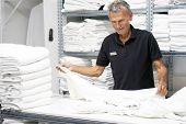 Elderly Caucasian Male Laundry Hotel Worker Folds A Clean White Towel. Hotel Staff Workers. Hotel Li poster