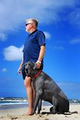 Man's best friend - man with his great dane dog on the beach