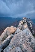 View of stones and rock formations from Ulsanbawi rock peak in stormy weather with clouds. Seoraksan poster