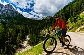 Single mountain bike rider on electric bike, e-mountainbike rides mountain trail. Man riding on e-bi poster