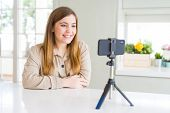 Beautiful young woman doing online video call using smartphone webcam with a happy and cool smile on poster