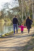 Family On A Walk In The Park. Father And Mom Holding Their Daughter Arms. Family Walk Down The Path  poster