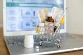Shopping Cart Toy With Medicaments In Front Of Laptop Screen With Pharmacy Web Site On It. Pills, Bl poster