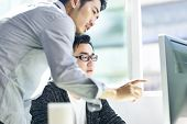 Two Young Asian Corporate Executives Working Together Using Desktop Computer. poster