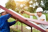 Two Professional Technicians Connecting Solar Photo Voltaic Panel To Metal Platform Using Screwdrive poster