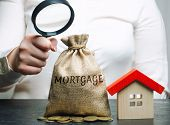 A Female Hand Is Holding A Magnifying Glass Over A Money Bag With The Word Mortgage And A Wooden Hou poster
