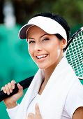Professional female tennis player with towel on her shoulders. Active pastime