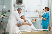 stock photo of intensive care  - Doctor checking heart beat of patient in bed with stethoscope with nurse adjusting I - JPG