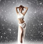 Fashion shoot of Aphrodite styled young woman over the snowy background