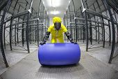 stock photo of bio-hazard  - fully protected in yellow uniform - JPG