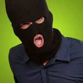 Burglar in face mask isolated on green background