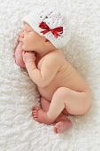 stock photo of sleepy  - Newborn Christmas baby girl asleep on a blanket - JPG