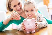 stock photo of coin bank  - Mother and daughter putting coins into piggy bank - JPG