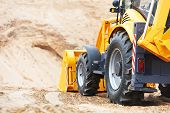 stock photo of backhoe  - Wheel loader Excavator with backhoe unloading sand at eathmoving works in construction site quarry - JPG