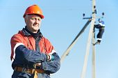 stock photo of lineman  - Portrait of electrician lineman repairman worker on electric post power pole line work - JPG