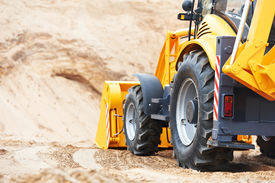 pic of backhoe  - Wheel loader Excavator with backhoe unloading sand at eathmoving works in construction site quarry - JPG