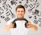 music and technology - young smiling man offering headphones