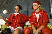 Two confident softball players sitting on the bench in dugout