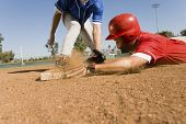 stock photo of infield  - View of a runner and an infielder reaching the base - JPG