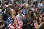 Group of multiethnic people singing American national anthem and holding American flags