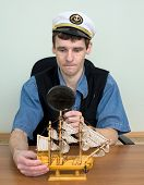 Guy In A Sea Cap With Toy Sailing Vessel