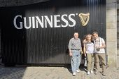DUBLIN, IRELAND - JUNE 7: Tourists' family posing in front of Guinness logo in Guinness Storehouse,