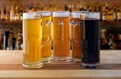 stock photo of 5s  - beer flight of five sampling mugs of light and dark craft beer in a bar - JPG