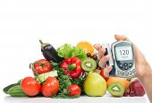 stock photo of tropical food  - Diabetes concept glucose meter in hand and healthy organic food fruits and vegetables organic green apple egg plant orange tomatoes cucumbers parsley kiwi grapefruit salad peach cherries on a white background - JPG