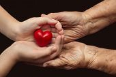 image of empathy  - little girl and elderly woman keeping red heart in their palms together symbol of care and love - JPG