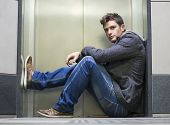 stock photo of elevator  - Handsome young man sitting in front of elevator  - JPG
