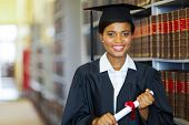 stock photo of laws-of-attraction  - pretty african university law school graduate on graduation day - JPG