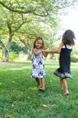 stock photo of mixed race  - Two beautiful mixed race sisters enjoying the park - JPG
